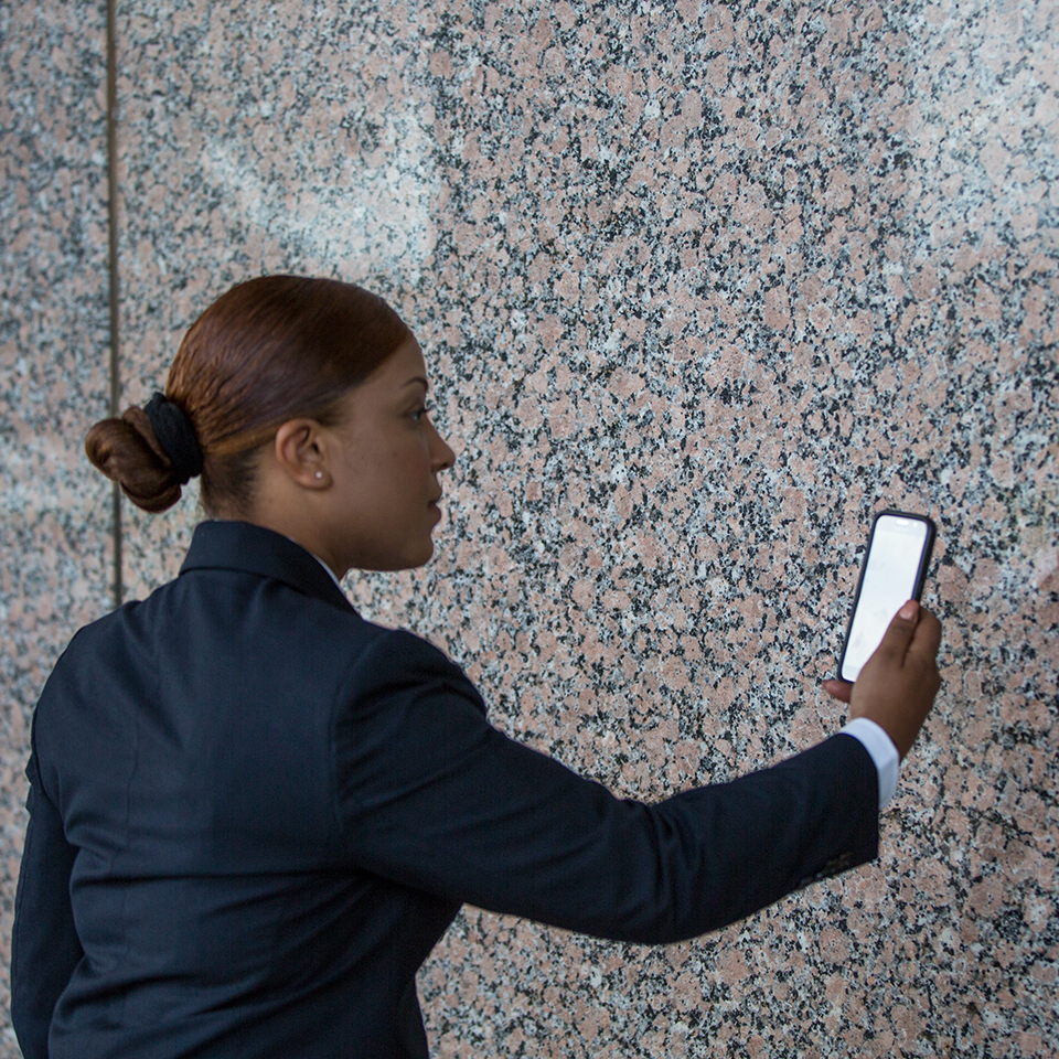 female security professional looking at mobile device