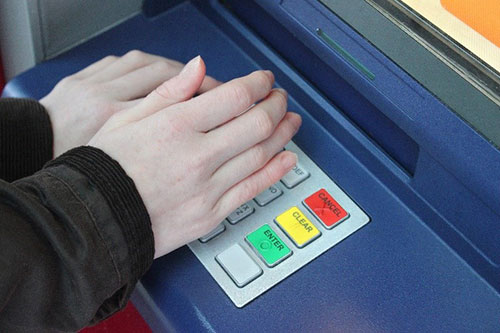Hands covering ATM keyboard
