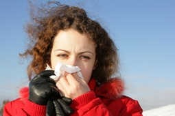 person holding tissue up to nose