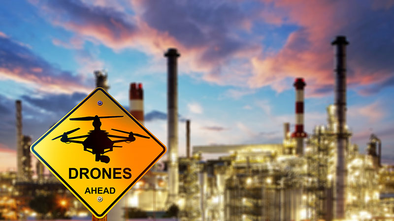 "Refinery with a ""drones ahead"" sign in front of it"